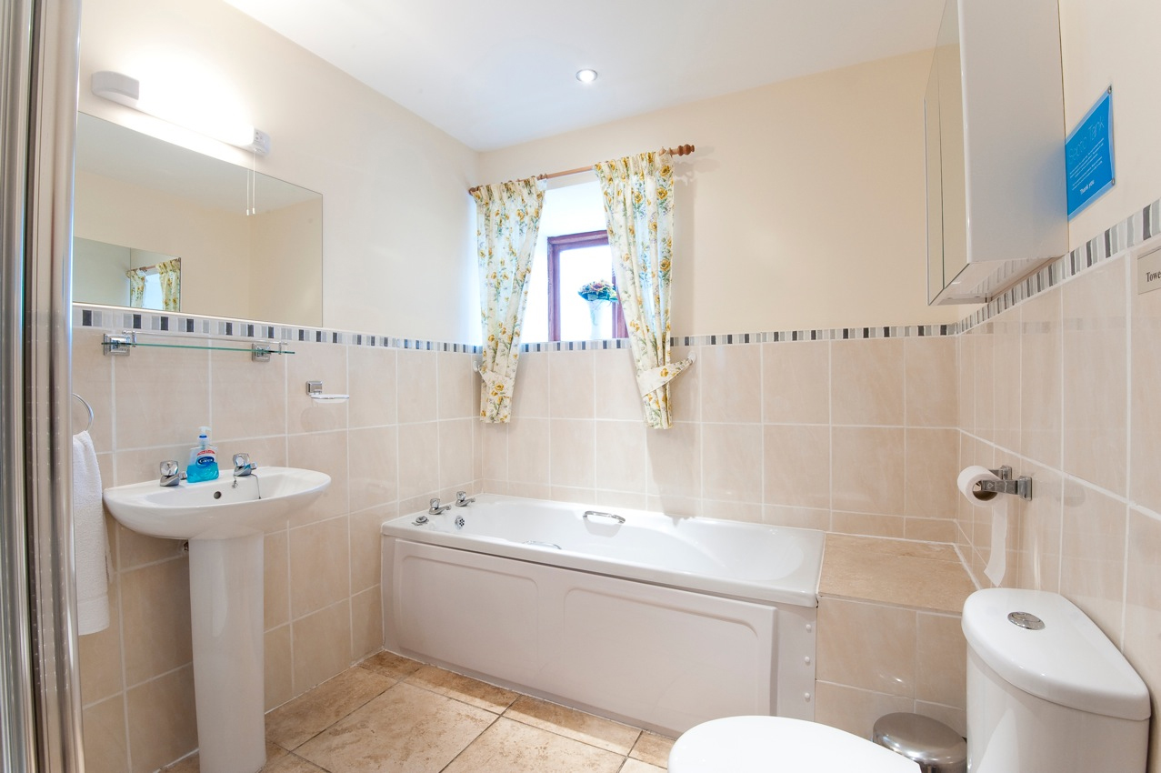 Spacious bathroom with shower cubical, bath, wash basin and toilet.t